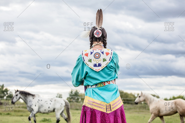 Native American girl in regalia watching horses run in a pasture