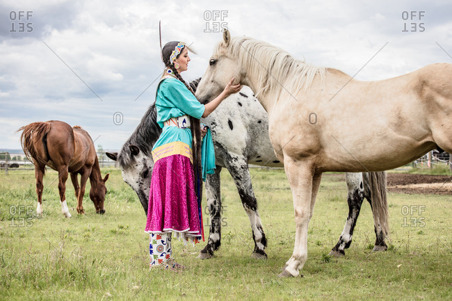 Native American girl in regalia with horses in a pasture