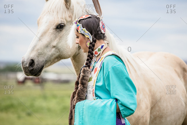 Native American girl in regalia with a tan horse in a pasture