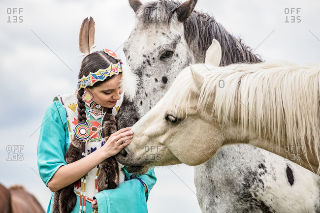 Native American girl in regalia petting horses in a pasture