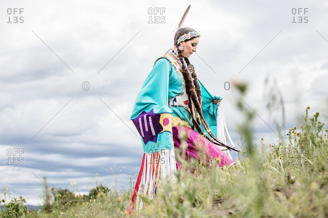 Young Native American woman in regalia walking in a field