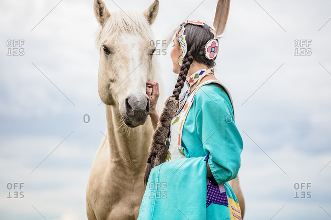 Native American girl in regalia petting a tan horse in a pasture