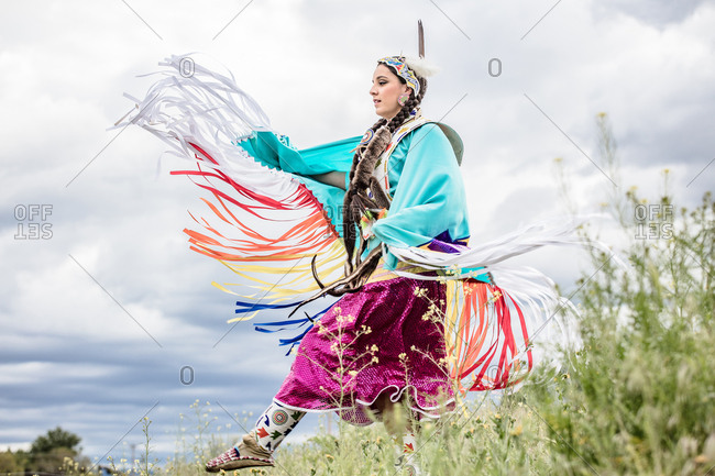 Young Native American woman in regalia dancing in a field