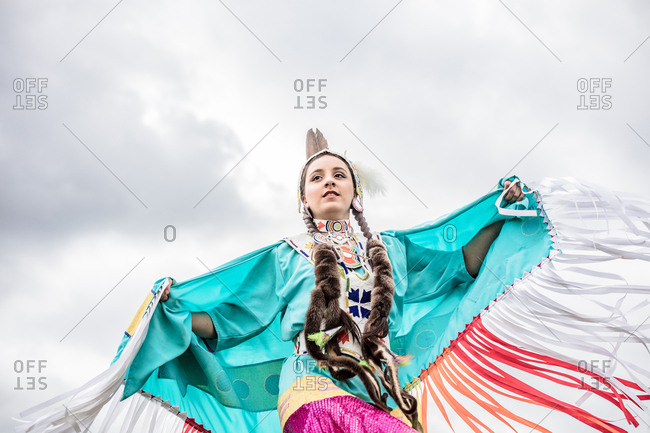 Native American girl in regalia dancing in a field