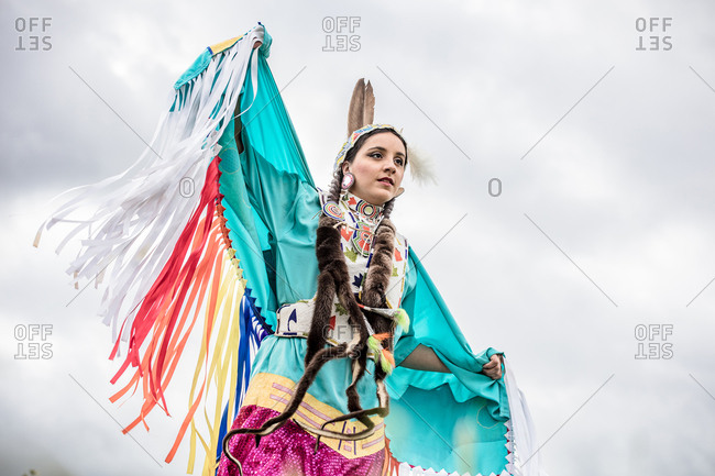 Native American girl dressed in regalia dancing in a field