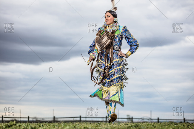 Young woman dressed in Native American regalia dancing in a field