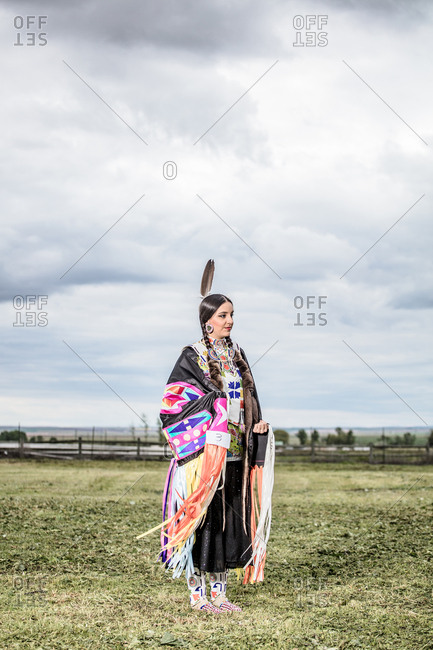 Young Native American woman in regalia standing in a field