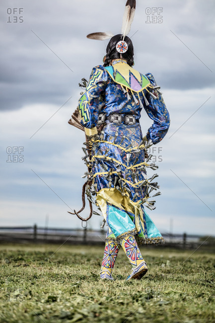 Rear view of young woman dressed in Native American regalia dancing in a field