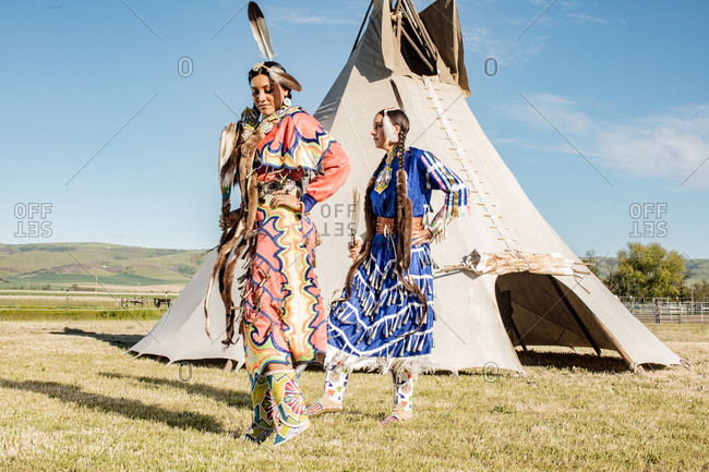 Young Native American sisters in regalia standing by a tipi