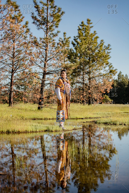 Native American woman in regalia walking at sunset by lake