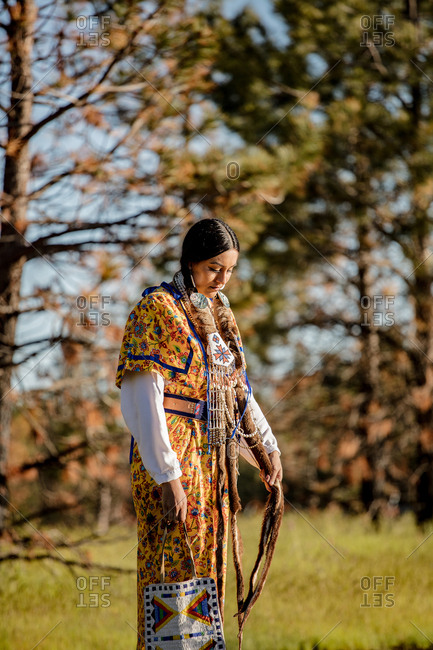 Native American woman in regalia walking at sunset by trees