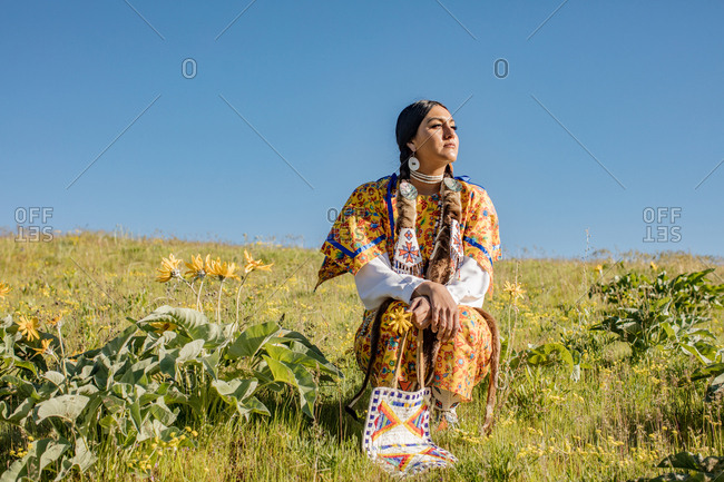 Young Native American woman in regalia sitting in a field by yellow flowers