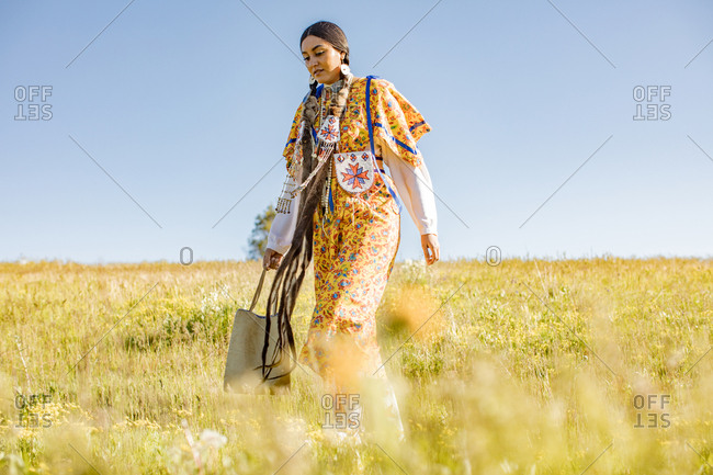 Native American woman in regalia walking in a sunny field