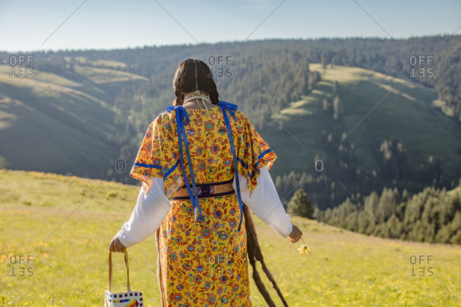 Rear view of Native American woman in regalia walking through hills at the Umatilla Reservation, Pendleton, Oregon