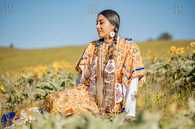 Young Native American woman in regalia relaxing in a field by yellow flowers