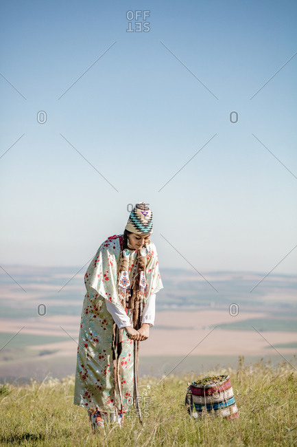 Native American woman in a pasture with digging stick