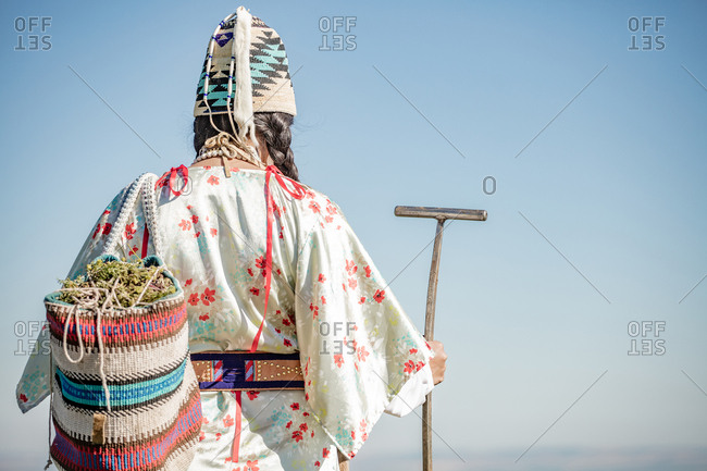 Native American woman walking with bag filled with edible plants and digging stick