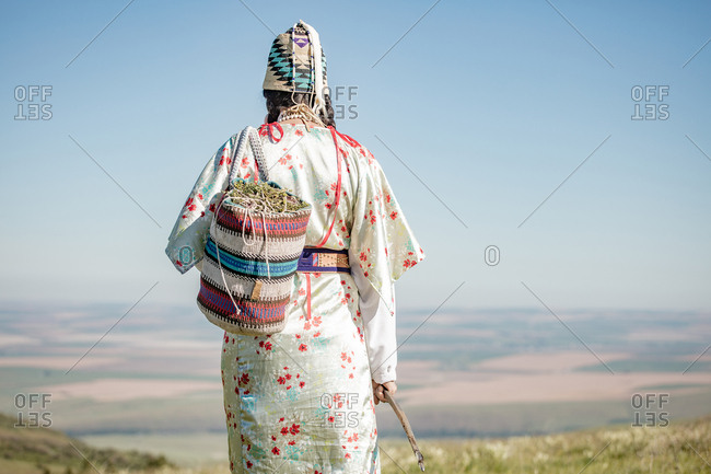 Rear view of Native American woman walking with bag filled with edible plants and digging stick