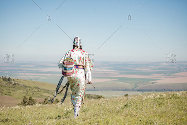 Native American woman walking on hill with bag filled with edible plants and digging stick
