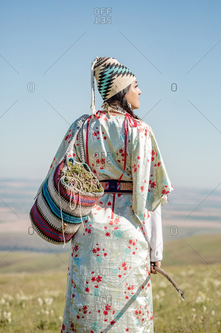 Rear view of Native American woman with bag filled with edible plants and digging stick