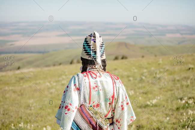 Rear view of Native American woman wearing beaded hat and carrying a bag filled with edible plants