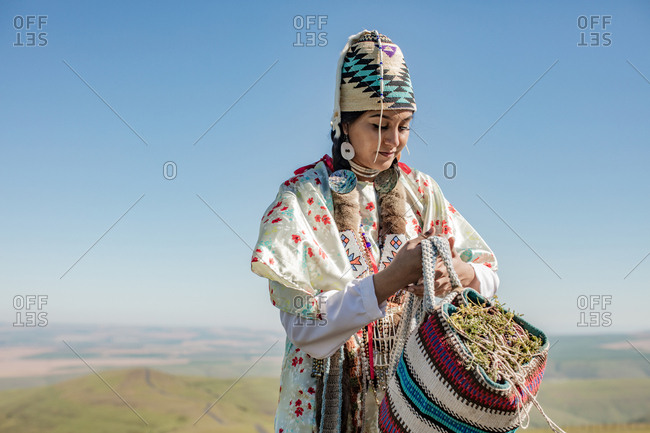 Native American woman dressed in regalia holding bag filled with edible plants