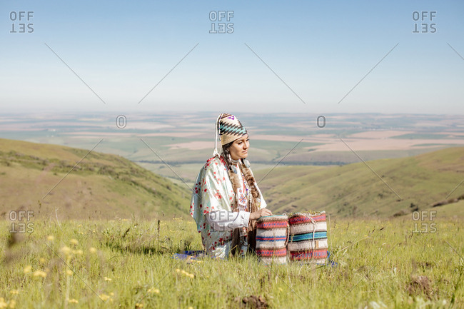 Native American woman sitting on a hill with bags filled with edible plants