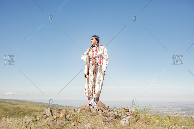 Young Native American woman dressed in regalia standing on hill looking away