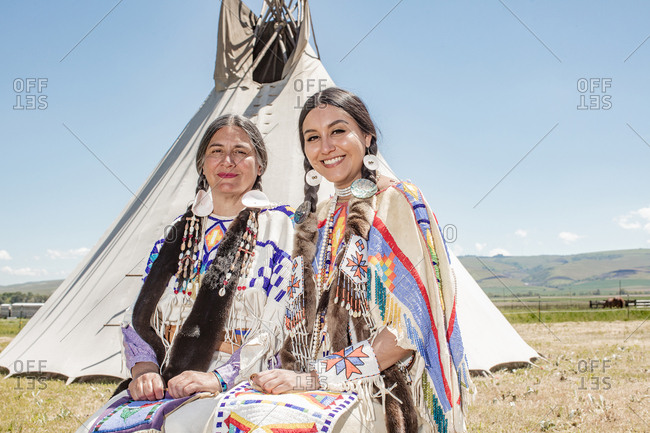 Native American mother and daughter in regalia sitting together by a tipi