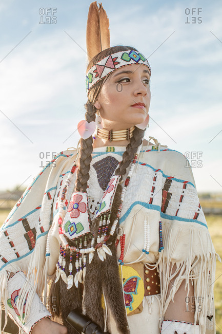 Native American girl dressed in regalia looking away
