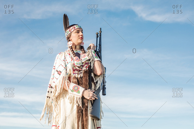 Young Native American girl dressed in regalia holding rifle