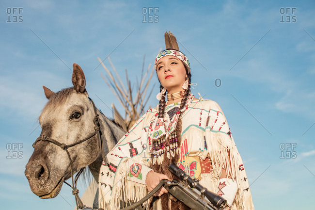 Young Native American girl dressed in regalia standing by horse holding rifle