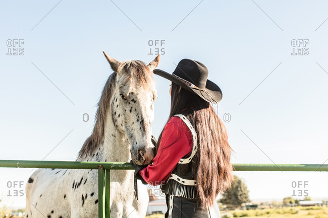 Girl wearing cowboy hat petting horse from behind