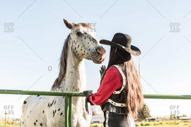Rear view of girl wearing cowboy hat petting horse