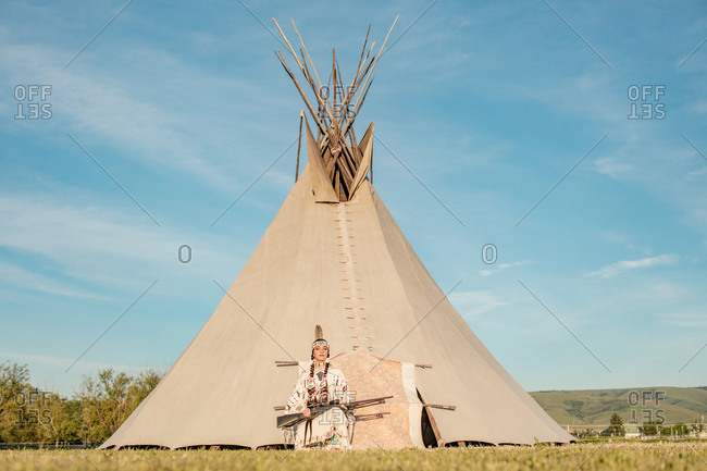 Woman from the Cayuse tribe with a rifle in front of a tipi