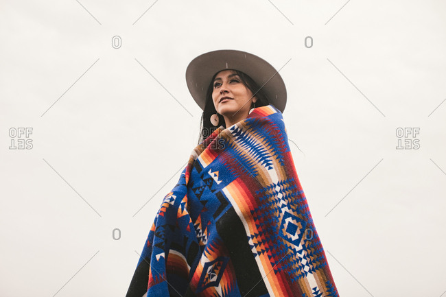 Low angle portrait of woman in hat and blanket