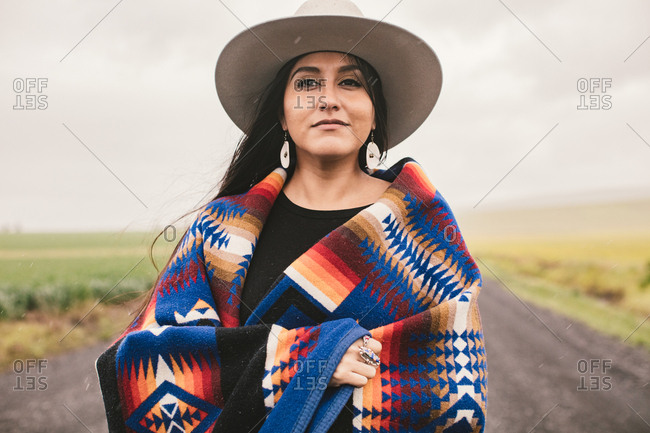 Beautiful young woman in a traditional American Indian blanket and hat