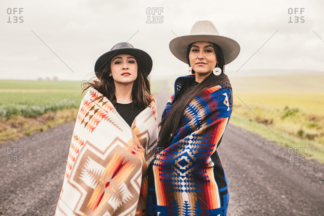 Portrait of two beautiful sisters in hats and blankets in road