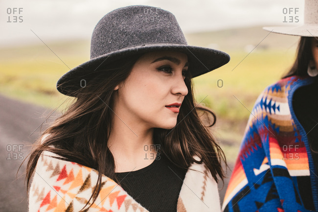 Portrait of young woman in western hat and blanket