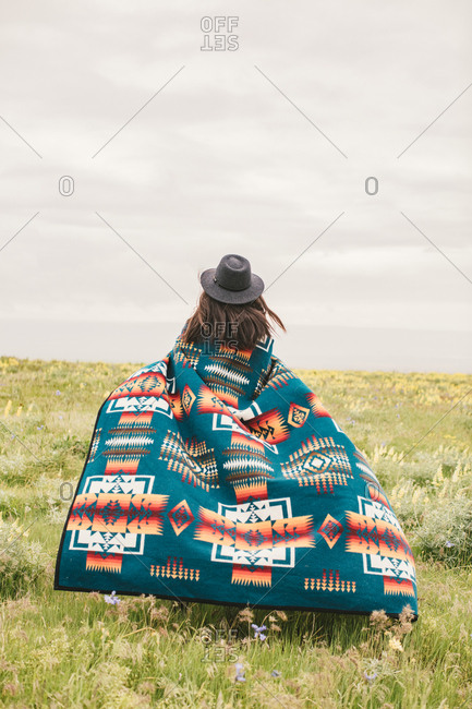 Woman wrapped in a colorful woven blanket in field