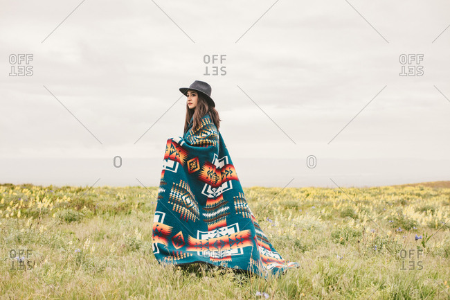 Woman in blanket and hat in field