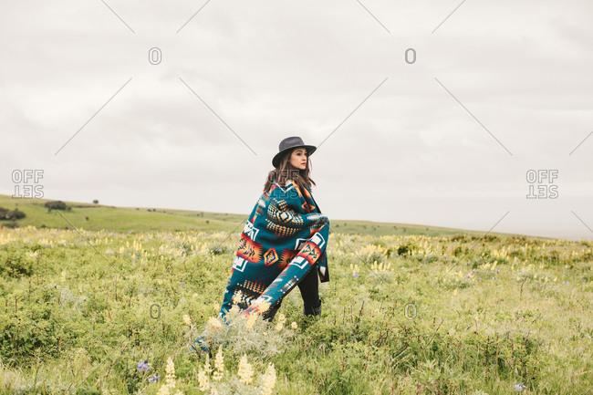 Woman in blanket and hat walking in field
