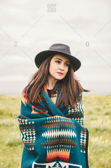 Beautiful young woman wearing hat and blanket in field