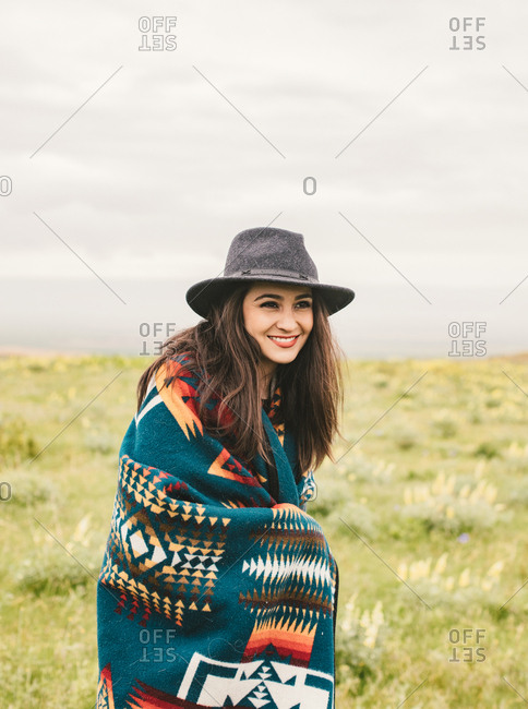 Smiling woman wearing hat and blanket in field