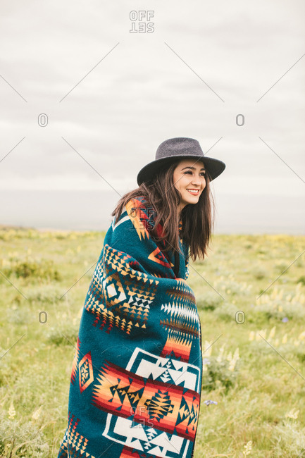 Portrait of a young woman wearing a western hat and woven blanket