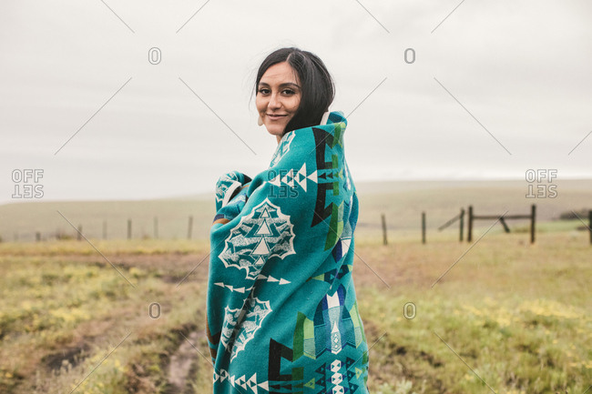 Smiling young woman wrapped in a blue woven blanket in field