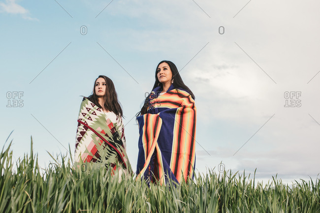 Two sisters wearing woven blankets standing in a field