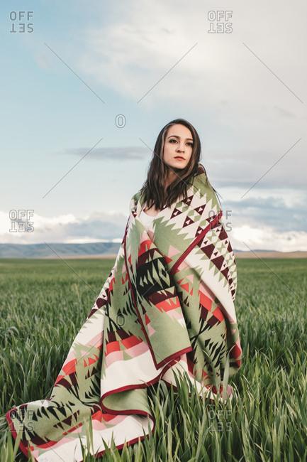 Woman wrapped in woven blanket in field