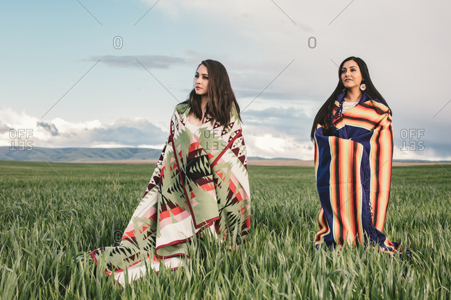 Two beautiful sisters wearing American Indian blankets in field