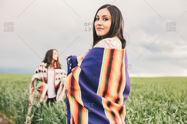 Two women wrapped in blankets standing in field on overcast day